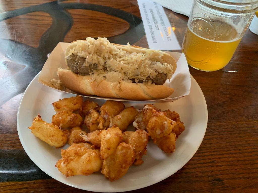 Cheese curds, brat with sauerkraut, and a Spotted Cow from New Glarus Brewing.